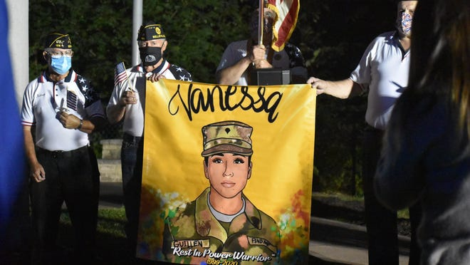 Members of the Belleville American Legion Post 105 hold a sign remembering soldier Vanessa Guillen, who was murdered while stationed at Fort Hood, at a candlelight vigil in Belleville on Sept. 14, 2020.