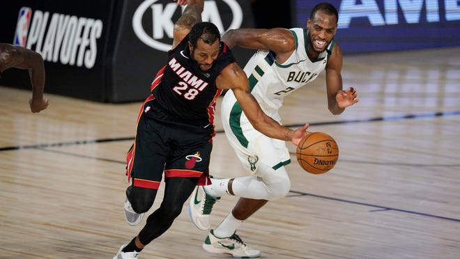 The Heat's Andre Iguodala (28) reaches for the ball in front of the Bucks' Khris Middleton during the first half Tuesday night.