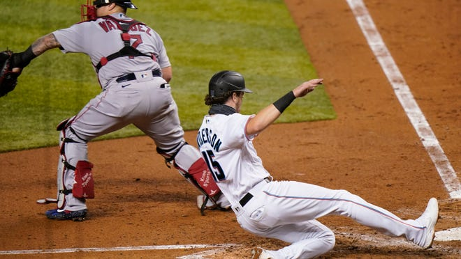 The Marlins' Brian Anderson slides in safely past Red Sox catcher Christian Vazquez with a run delivered by Lewis Brinson's third-inning double on Wednesday night in Miami.