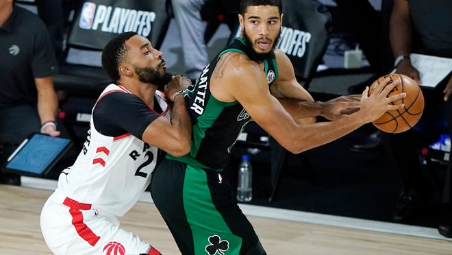 The Celtics' Jayson Tatum, right, looks to drive past the Raptors' Norman Powell during the first half Sunday.