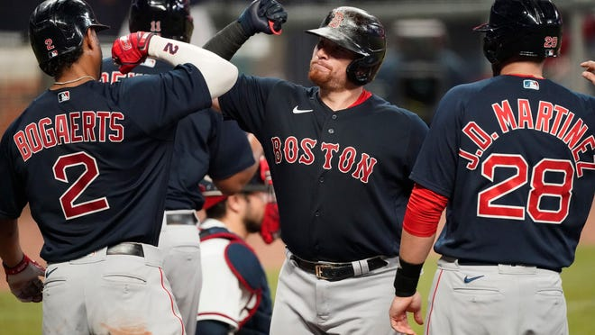 Red Sox catcher Christian Vazquez, center, celebrates with Xander Bogaerts and J.D. Martinez after hitting a grand slam in the second inning Saturday night in Atlanta.