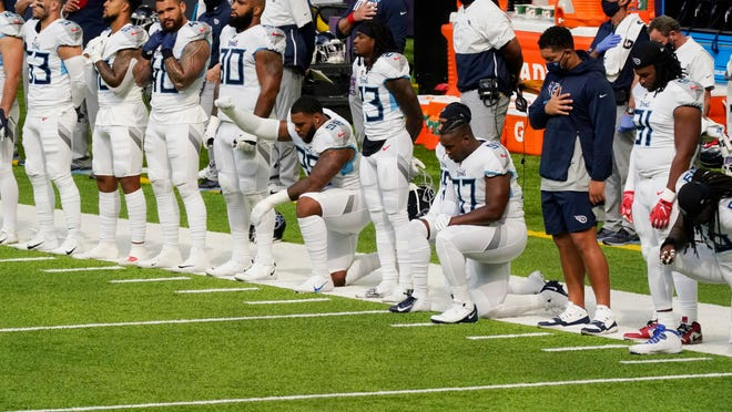 Members of the Tennessee Titans take part in the national anthem before an NFL football game against the Minnesota Vikings, Sunday, Sept. 27, 2020, in Minneapolis. The NFL says the Tennessee Titans and Minnesota Vikings are suspending in-person activities after the Titans had three players test positive for the coronavirus, along with five other personnel. The league says both clubs are working closely with the NFL and the players' union on tracing contacts, more testing and monitoring developments. The Titans are scheduled to host the Pittsburgh Steelers on Sunday.