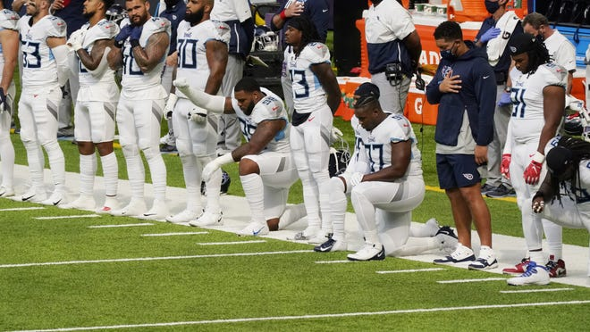 Members of the Tennessee Titans take part in the national anthem before their game against the Minnesota Vikings on Sunday.