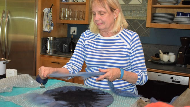 Artist Barbara Attwell spreads out raw wool on a plastic model during the wet felting process.