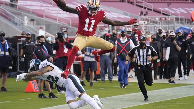San Francisco 49ers wide receiver Brandon Aiyuk hurdles Philadelphia Eagles safety Marcus Epps on his way to scoring a touchdown Sunday night. He'll be a hot waiver wire option this week.
