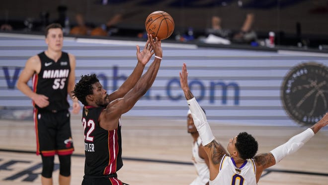 Miami Heat's Jimmy Butler (22) shoots against Los Angeles Lakers' Kyle Kuzma (0) during the second half in Game 3 of basketball's NBA Finals, Sunday, Oct. 4, 2020, in Lake Buena Vista, Fla.