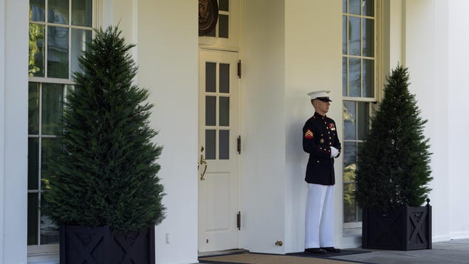 A Marine is posted outside the West Wing of the White House Wednesday, signifying the President is in the Oval Office.