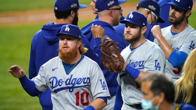 Los Angeles Dodgers' Justin Turner (10) and his teammates celebrate after defeating the San Diego Padres 12-3 in Game 3 of a baseball National League Division Series. early Friday, Oct. 9, 2020, in Arlington, Texas.
