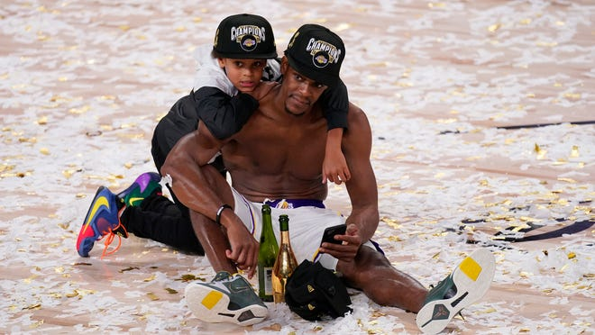 Rajon Rondo takes in the moment Sunday night amid the confetti with his son Rajon Jr. after the Lakers defeated the Heat to win the NBA Finals.