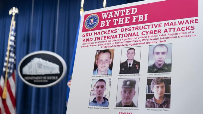 A poster showing six wanted Russian military intelligent officers is displayed before a news conference at the Department of Justice, Monday, Oct. 19, 2020, in Washington.