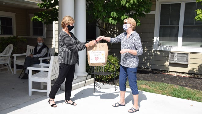 Cindy Zomar, right, drops off cards to Donna Lussier, receptionist at the Christopher Heights assisted living facility in Marlborough, earlier this week. City resident Mark Vital created the program to put a smile on the faces of Marlborough seniors.