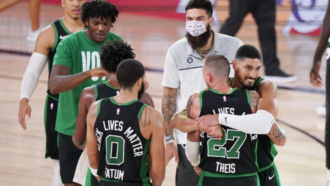 Boston Celtics players celebrate after beating the Miami Heat 121-108 in an NBA conference final playoff basketball game Friday, Sept. 25, 2020, in Lake Buena Vista, Fla.