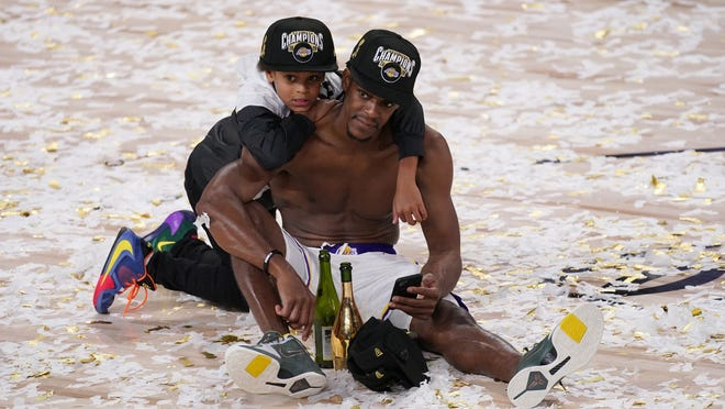 Los Angeles Lakers guard Rajon Rondo sits in confetti with his son Rajon Jr. after the Lakers defeated the Miami Heat, 106-93, in Game 6 of the NBA Finals Sunday in Lake Buena Vista, Fla.
