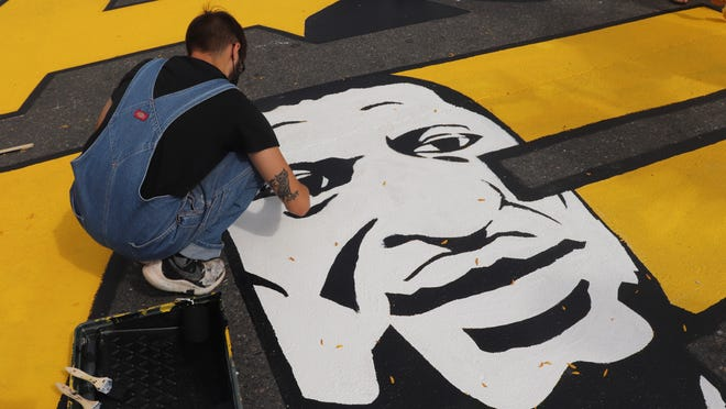 Anthony Araujo-Amaral, who led the design of the street mural, works on the portrait of George Floyd in Magoun Square on Sept. 27, 2020.