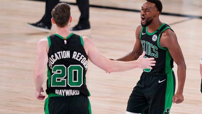 Boston Celtics' Gordon Hayward (20) and Kemba Walker (8) celebrate after a play against the Miami Heat during the second half of an NBA conference final playoff basketball game Friday, Sept. 25, 2020, in Lake Buena Vista, Fla. The Celtics won 121-108.