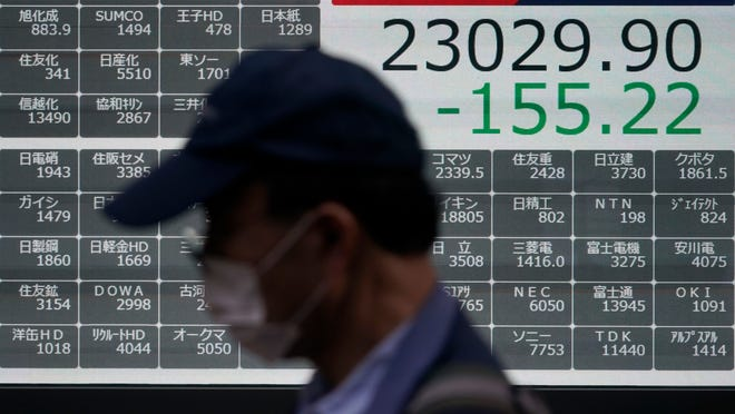 A man walks past an electronic stock board showing Japan's Nikkei 225 index at a securities firm in Tokyo Friday, Oct. 2, 2020. U.S. stock futures and Asian shares have fallen after U.S. President Donald Trump said he and first lady Melania Trump tested positive for the coronavirus.