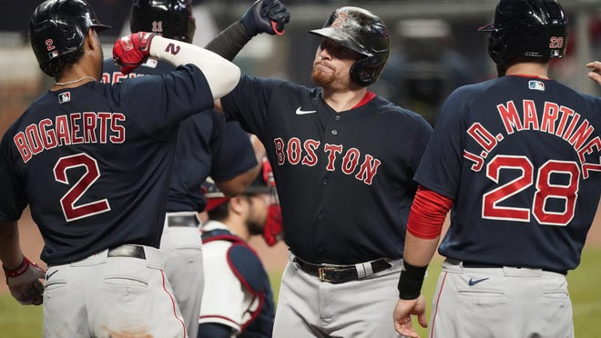Red Sox catcher Christian Vazquez (center) celebrates with Xander Bogaerts (left) and J.D. Martinez after he hit a grand slam in the second inning of a baseball game against the Atlanta Braves on Saturday, Sept. 26, 2020, in Atlanta.