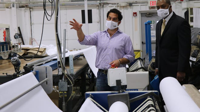 Matouk CEO George Matouk and Superintendent of Providence Public Schools Harrison Peters tour the Fall River manufacturing facility. They are wearing samples of the masks that will be donated to Providence Schools.