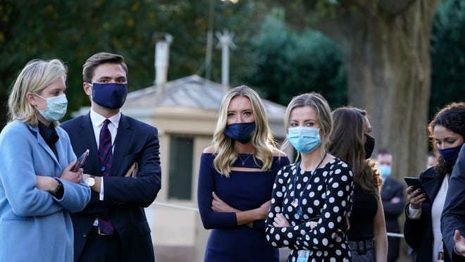 White House press secretary Kayleigh McEnany, third from left, waits with others as President Donald Trump prepares to leave the White House to go to Walter Reed National Military Medical Center after he tested positive for COVID-19, Friday, Oct. 2, 2020, in Washington.
