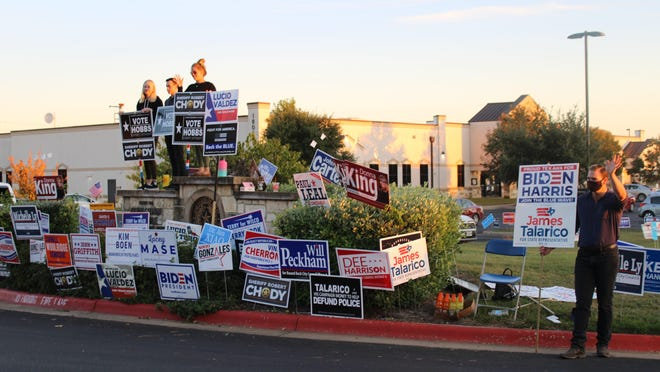 Volunteers hold campaign signs and greet cars at the front of the Williamson County Annex Center as they enter to vote on Tuesday.