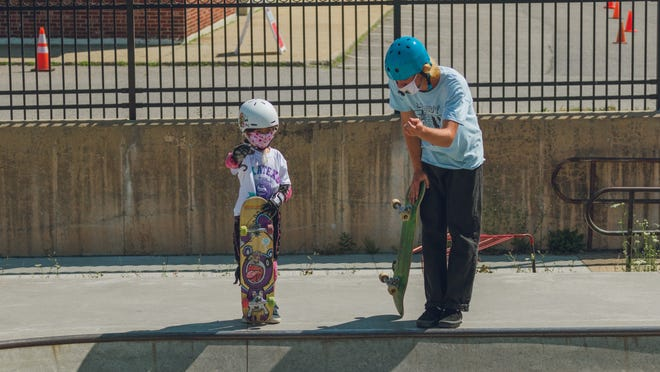 Skateboard counselor Evan O'Cain gives instruction to Kairi Stanbrook.