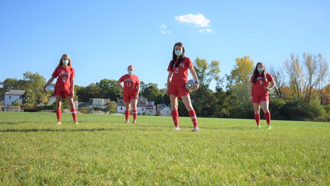 Saugus girls' soccer seniors Haley McLaughlin (15), Jess Carter (13), Megan Bluette (2) and Keila Friend (9), from left, are shown lining up for a photo opportunity, while exercising the proper amount of social distancing on the pitch.