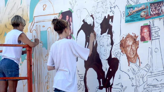"""Former Ballhawk player Mary Jane """"Snookie"""" Werderman observes a painter outlining the mural to be painted this week."""