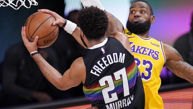 Denver Nuggets' Jamal Murray (27) drives against Los Angeles Lakers' LeBron James (23) Thursday in Lake Buena Vista, Fla.