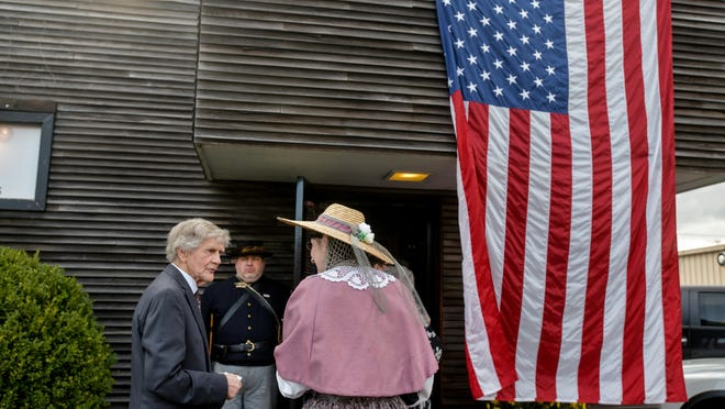 """Civil War re-enactor Robert Leinweber of Easton, in background, stands guard while Peoria historian Norm Kelly chats with Linda Aylward of Peoria outside Paparazzi Italian restaurant before a fundraising dinner for the Peoria Civil War """"Shaft"""" memorial on April 7, 2019, in Peoria Heights."""
