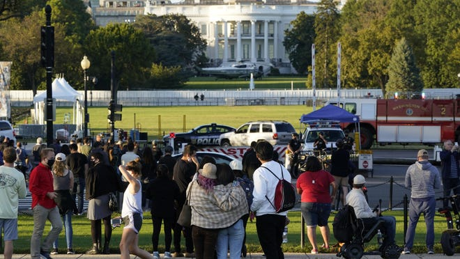 People look toward The White House as Marine One waits on the South Lawn to carry President Donald Trump to Walter Reed National Military Medical Center, Friday, Oct. 2, 2020 in Washington.