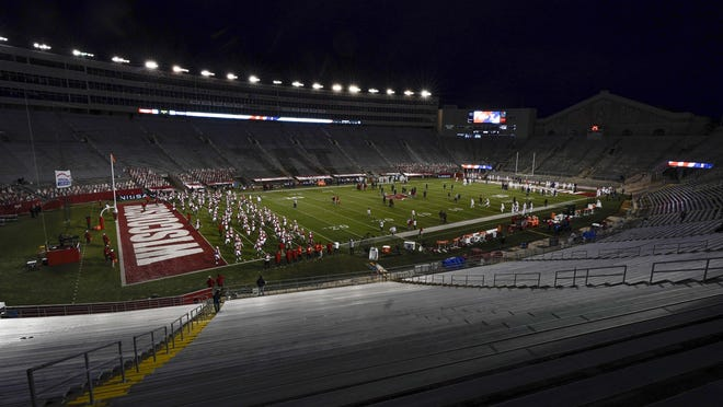 The seats at Camp Randall Stadium are empty as players warm up before a Big Ten Conference football game Friday between Wisconsin and Illinois in Madison, Wis.