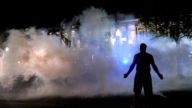 A protester attempts to continue standing through a cloud of tear gas fired by police outside the Kenosha County Courthouse on Monday in Kenosha, Wis. Protesters converged on the county courthouse during a second night of clashes after the police shooting of Jacob Blake a day earlier turned Kenosha into the nation's latest flashpoint city in a summer of racial unrest.