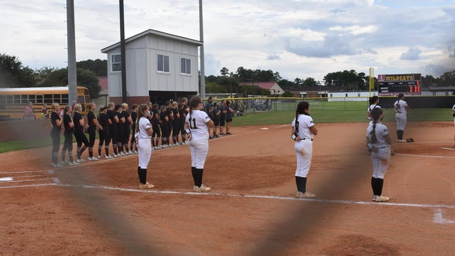 Richmond Hill softball players social distance during the national anthem before a home game against South Effingham.