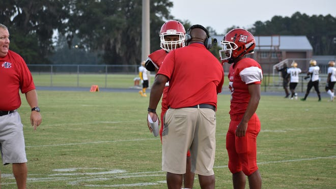 Cherard Freeman talks with Jamari Flannel (left) and Jacari Carney (5, on right) about what play to run against Butler on Friday night in Freeman's regular-season debut as Bryan County's head coach.