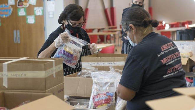 Cana Padilla, a food service worker at Jardine Elementary School, reaches to fill one of hundreds of brown bags with seven breakfasts and seven lunches Tuesday afternoon in the school cafeteria.