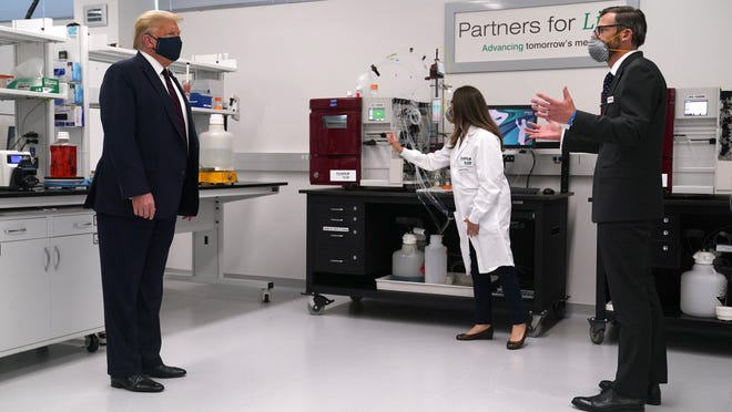Fujifilm Diosynth Biotechnologies CEO Martin Meeson, right, talks with President Donald Trump as he tours a company facility Monday in Morrisville, N.C. Trump announced that a $265 million grant will go to a manufacturing facility run by Fujifilm and the Texas A&M University System to produce the coronavirus vaccine next year.
