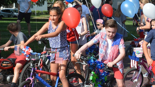 Ella Carter, 10, left, and Jacob Zeller, 10, ride festive bicycles in the annual Potwin Fourth of July Parade.