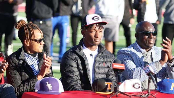 UGA football commit Smael Mondon Jr. sits alongside his mother Dissa Mondon, left, and father Smael Mondon Sr., right, just after he announced his commitment to UGA.