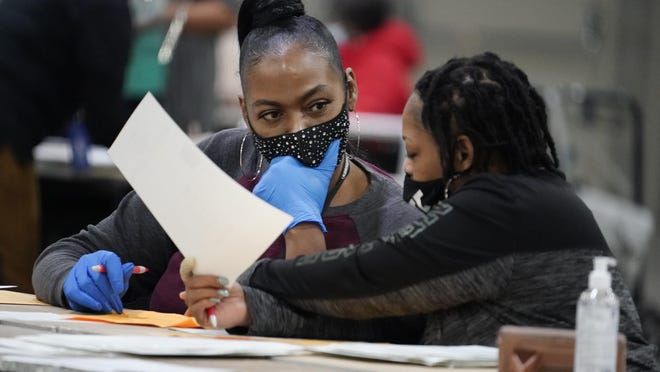 Officials sort ballots during an audit at the Georgia World Congress Center on Saturday, Nov. 14, 2020, in Atlanta. Election officials in Georgia's 159 counties are undertaking a hand tally of the presidential race that stems from an audit required by state law.