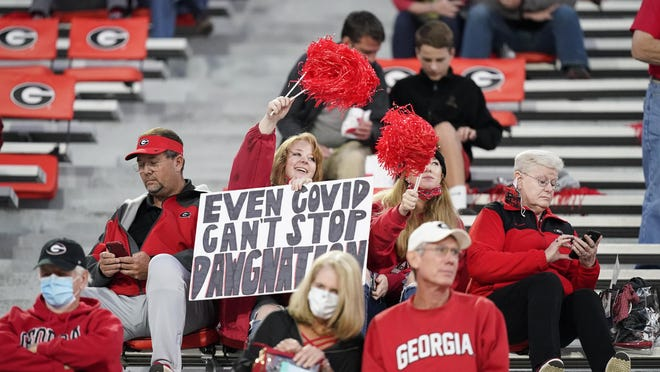 """FILE  - In this Oct. 3, 2020, file photo, a fan holds a sign """"Even COVID can't stop Dawgmation"""" before an NCAA college football game, in Athens, Ga. Coaches wearing masks around their chins. Fans not wearing masks at all while cheering from their seats. One school deciding to drop the safety checks it was requiring for those entering the stadium to cut down on long lines. College football is sending plenty of alarming signals at it attempts to get through a tenuous season amid a pandemic."""