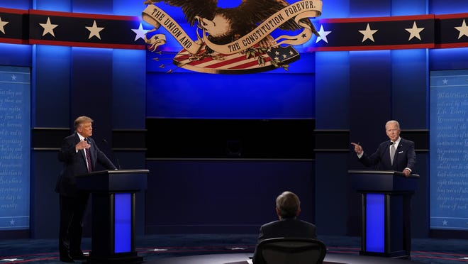 President Donald Trump, left, and Democratic presidential candidate former Vice President Joe Biden, right, with moderator Chris Wallace, center, of Fox News during the first presidential debate Tuesday at Case Western University and Cleveland Clinic in Cleveland, Ohio.