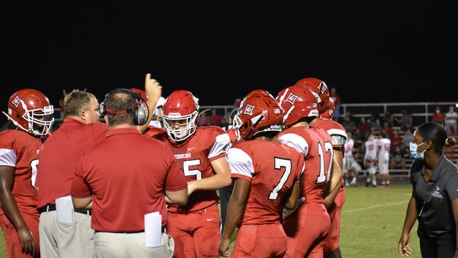 Bryan County defensive coordinator Ron Lewis talks to the defense as Kadrian Lee (7), Brayden Butler (17) listen on Friday night in the game against Screven County in Pembroke.
