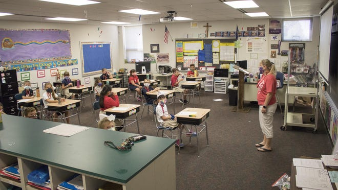 Second-graders in Michelle Ireland's class sit at desks spaced 6 feet apart Wednesday morning at Christ the King Elementary School. Several area private schools, including Christ the King, returned to in-person classes this week.