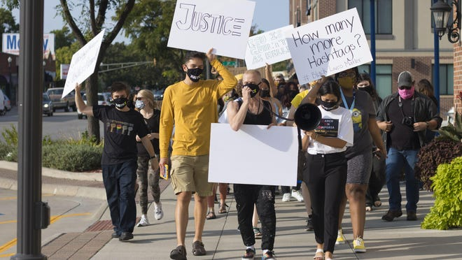 Emporia State University students and community members march along Commercial Street in Emporia to protest what they called inadequate action after two former university employees sued the university for retaliating when they reported racial discrimination.