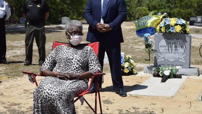Ahmaud Arbery's grandmother Ella Cooper sits feet from her grandson's grave as she remembers him at a news conference Tuesday at the New Springfield Baptist Church cemetery in Burke County where Arbery is buried.