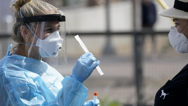 FILE - In this Aug. 13, 2020, file photo, nurse practitioner Debbi Hinderliter, left, collects a sample from a woman at a coronavirus testing site near the nation's busiest pedestrian border crossing in San Diego. U.S. health officials have sparked a wave of confusion after posting guidelines that coronavirus testing is not necessary for people who have been in close contact with infected people.
