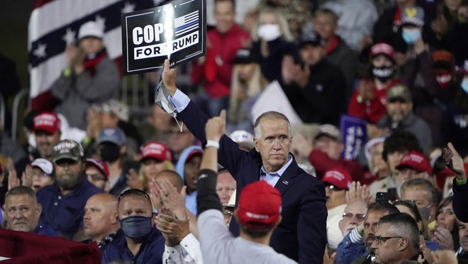 Sen. Tom Tillis, R-N.C., holds a sign as President Donald Trump speaks at a campaign rally, Saturday at Fayetteville Regional Airport in Fayetteville.