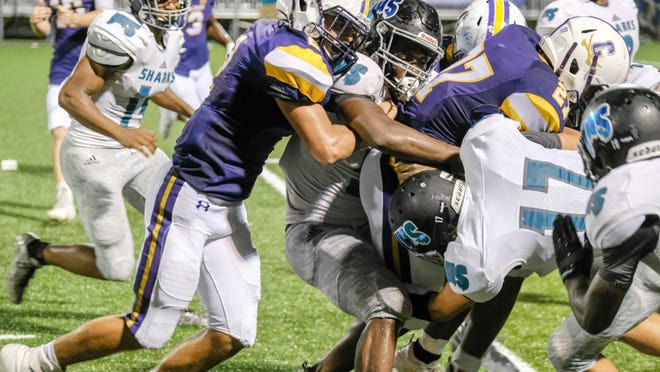 Former Calvary standout Jalen Leary (27) keeps charging with a host of Islands defenders working to bring him down in a 2018 game. (ROBERT COOPER/SAVANNAHNOW.COM]
