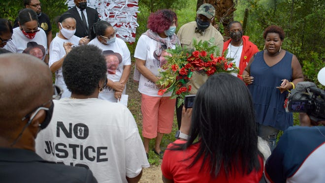 Decatur attorney Mawuli Mel Davis, a co-counsel for the Lewis family, presents a wreath to the mother of Julian Lewis, Lindsay Mae Milton Lewis, last Saturday at the scene on Stoney Pond Road where the 60-year-old was shot and killed by a state trooper.