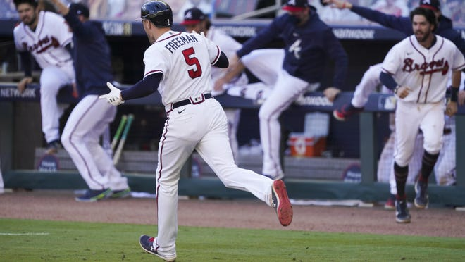 Atlanta Braves Freddie Freeman runs to first base after hiting a game-winning base hit against the Cincinnati Reds in the 13th inning during Game 1 of a National League wild-card baseball series Wednesday in Atlanta. The Atlanta Braves won 1-0.